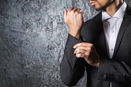 cuff: Man in beautiful suit buttoning cuff sleeve