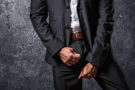 Man in suit zip his pants up