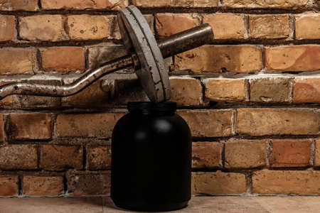 albumin: Barbell and jar with protein against brick wall Stock Photo