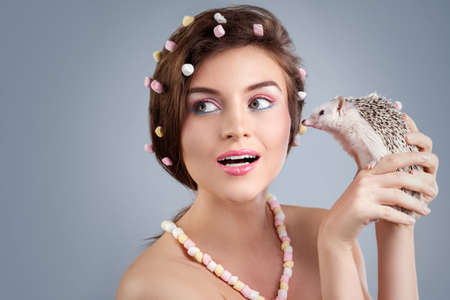Beautiful woman in creative image with marshmallow with hedgehog