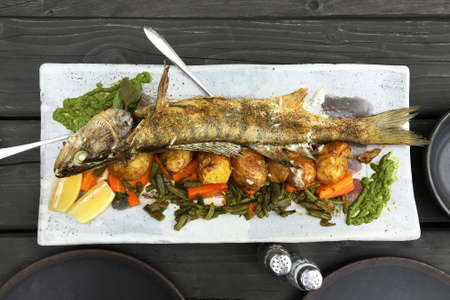 pikeperch: Whole baked fish with vegetables on the table