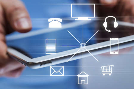 Hands with a tablet and different icons around. Omni channel Standard-Bild