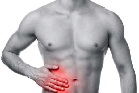 digestion: Man with pain in his stomach isolated on white background. Problems with organs of digestion. Stock Photo