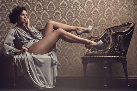 Hermosa mujer en hermoso vestido sentado en la silla