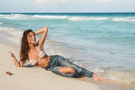Jonge charmante vrouw in natte jeans op het strand