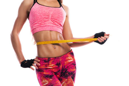 Fitness girl and measure tape on white background
