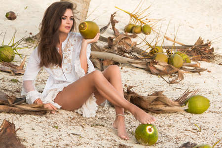 Beautiful woman and lot of coconuts on the ground