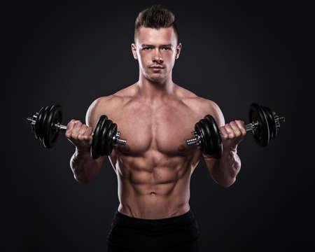 Bodybuilder joven haciendo ejercicios con pesas Foto de archivo - 85172821