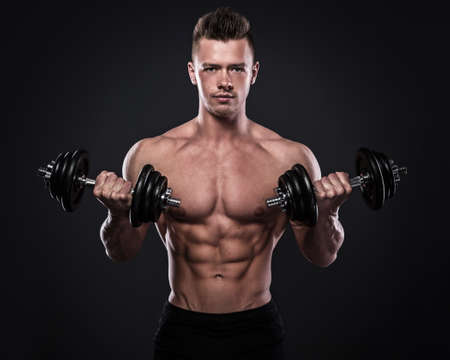 Young bodybuilder doing exercises with dumbbells