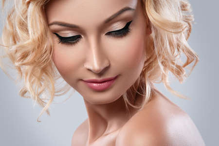 Beautiful blonde woman with eyeliner on her eyes in studio Stock Photo