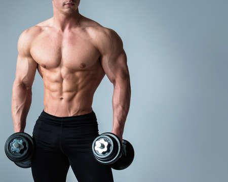 Young bodybuilder with dumbbells in studio