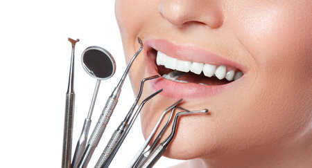 scaler: Female smile and detnal tools on white background