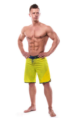 sixpack: Young fitness model in green shorts over white background Stock Photo