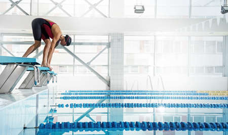 Professional woman swimmer in a starting position