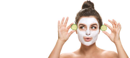 Woman with facial mask and cucumber slices in her hands on white background Foto de archivo
