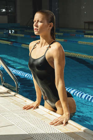Attractive woman swimmer on the poolside