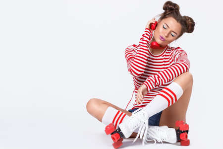 Beautiful woman in the roller-skates is listening music in studio Stock Photo