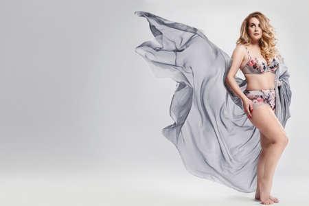 Modelo de talla grande con lencería y pieza de tela ondeando en estudio