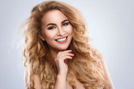 Portrait of beautiful blonde woman with curly hair in studio Stock Photo