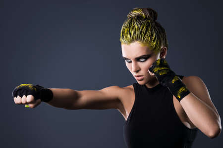 Woman mma fighter with yellow hair in studio