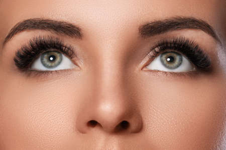 Female face with beautiful eyebrows and artificial eyelashes for maximum volume