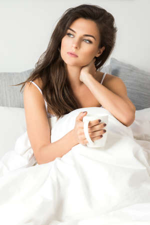 Sick woman sitting under a blanket with a cup of hot drink
