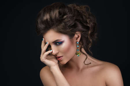 Portrait of gorgeous woman with beautiful hairdo and shiny earrings in studio