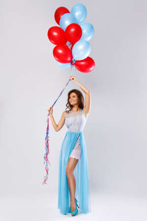 Lovely woman wearing beautiful dress with a lot of colorful balloons in studio