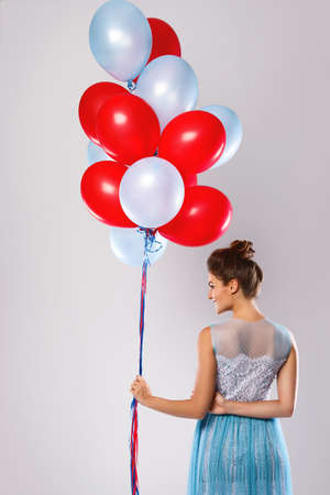Woman wearing beautiful dress with a lot of colorful balloons  in studio