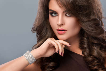 Portrait of gorgeous woman with beautiful makeup and hairdo Фото со стока