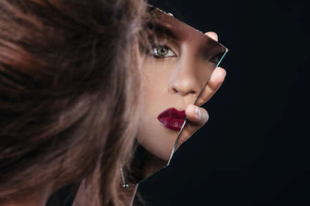 Beautiful woman looking in the piece of mirror Imagens