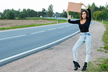 Young woman hitchhiker on the road is holding a blank cardboard sign Foto de archivo