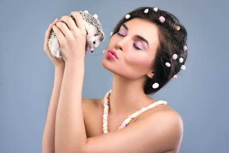 Beautiful woman with a creative hairstyle which made from marshmallow is holding a cute little hedgehog