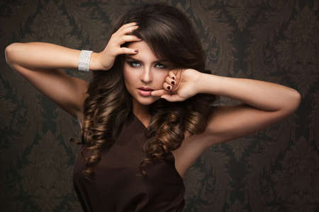 Gorgeous woman with beautiful makeup and hairdo, wearing a beautiful brown dress.