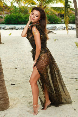 Lovely woman in beautiful dress with wild print on the beach