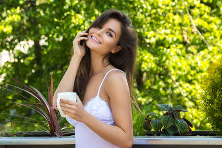 Happy young woman drinking coffee on the balcony or in the garden