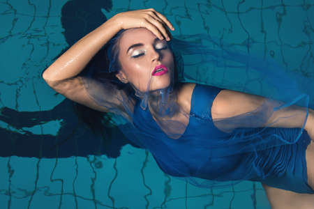 Fashion portrait of beautiful woman in swimming pool