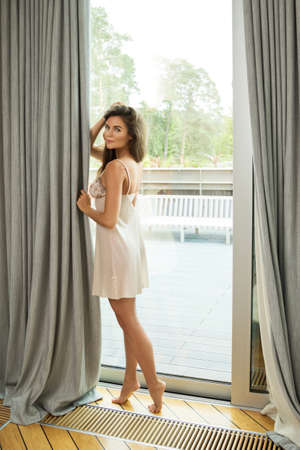 Young and beautiful woman beside a window at the morning Stock Photo