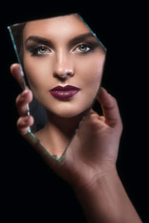 Hand holding a splinter of mirror with female face in reflection Foto de archivo