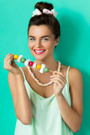 Happy woman with colorful makeup and sweet candies on skewer against cyan background