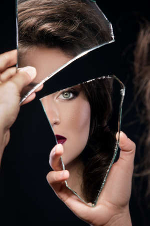 Beautiful woman looking in the piece of mirror Banque d'images