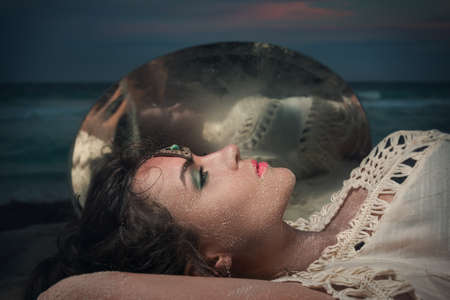Beautiful woman lying on the beach beside a mirror in the darkness Stock Photo