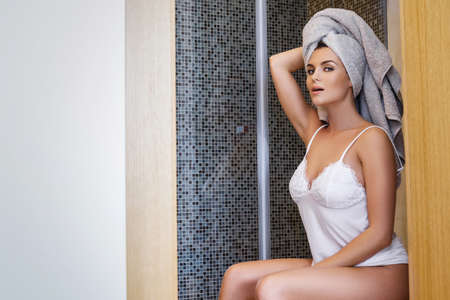 Woman with towel on her head sitting on the toilet at early morning Stock Photo