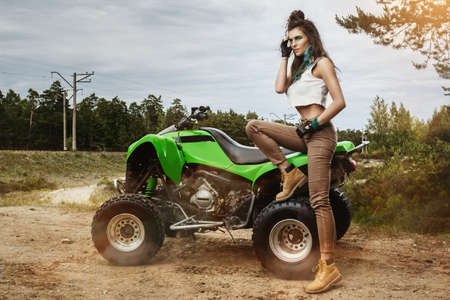 Stylish and beautiful woman and ATV on the off-road