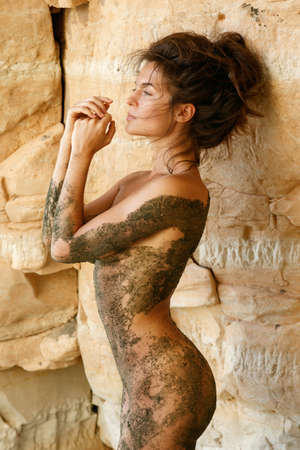 Naked woman covered with a mud beside sea caves