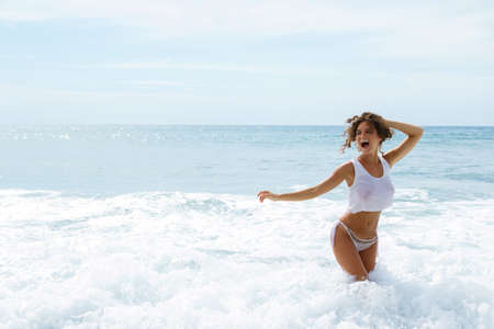 Beautiful woman in a white wet shirt in the sea