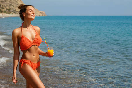 Beautiful woman on the beach with a glass of cocktail Stock Photo