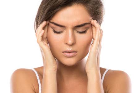 Woman with a headache on white background Фото со стока