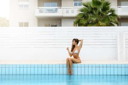Beautiful woman in bikini is sitting beside a swimming pool Stok Fotoğraf
