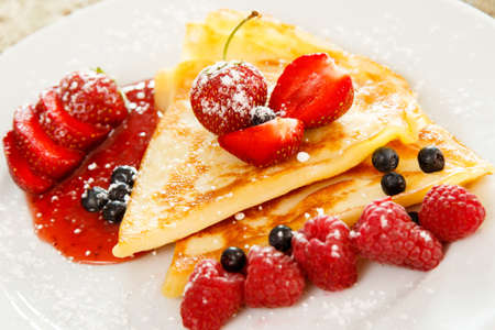 Pancakes with berries and sugar powder on the plate
